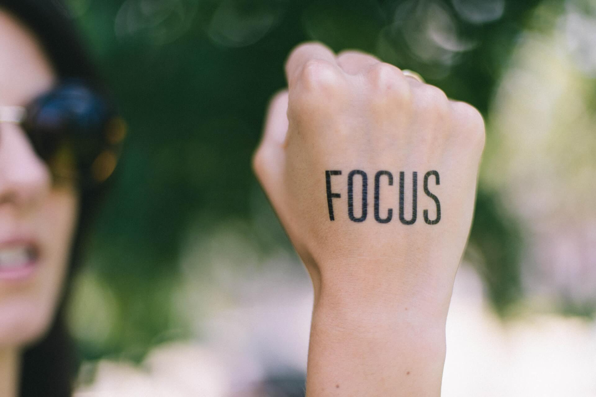 focus stamped on womans hand